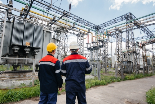 Two specialist electrical substation engineers inspect modern hi - Two specialist electrical substation engineers inspect modern high-voltage equipment. Energy. Industry - ©Andrii - stock.adobe.com